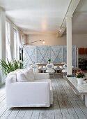 Sofa mit weissem Bezug auf schlichten Dielenboden, im Hintergrund Essplatz vor Raumteiler
