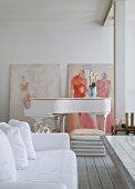 Sofa mit weisser Husse und Klavier in offenem Wohnbereich mit geweisselter Ziegelwand, moderne Gemälde