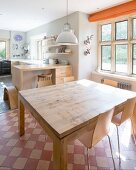 Solid-wood dining table and modern chairs on vintage chequered floor in spacious kitchen