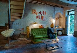 Vintage sofa with green velvet cover next to foot of winding staircase in open-plan interior of rustic country house