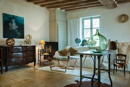 Green demijohn on table, coffee table, sofa and antique chest of drawers in rustic interior
