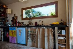 Quirky kitchen counter with coffee-sack curtains and hand-made doors