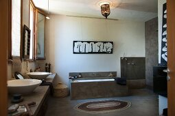 Ethnic-style bathroom with countertop sinks, masonry bathtub and open-plan shower area