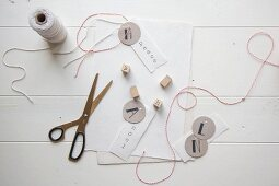 Making gift tags using paper, scissors, thread and stamps