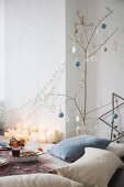 Festive picnic in living room with bare branch used as Christmas tree and many candles