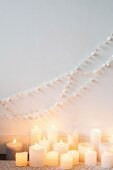 Garland of white paper discs on wall above lit candles