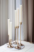 Five white candles with extinguished wicks in bronze candlesticks on marble board