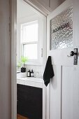 View of tiled washstand with black base unit seen through open bathroom door in period apartment