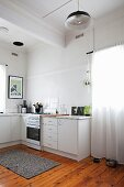 Simple, white base units, retro lamp and old wooden floor in kitchen