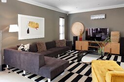 Modern corner couch and yellow chaise on black and white rug in living room with grey-painted walls