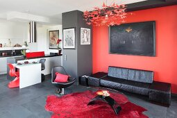 Black leather couch below artwork on red wall, coffee table on red rug and tiled floor and kitchen area in background