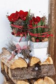 Two arrangements of thuja branches and amaryllis in small flower pots on top of stacked firewood