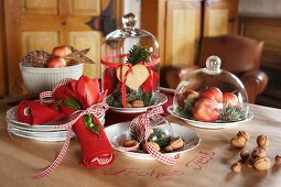 Plates of nuts, apples and pine cones under glass covers on festive table