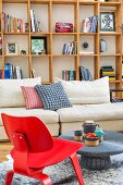 Red, classic chair and rustic coffee table in front of pale sofa and wooden shelving against wall in modern living room