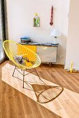 Yellow, retro, string easy chair with metal frame in front of 50s-style sideboard