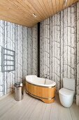 Wooden bathtub and toilet in corner of modern bathroom with tree-patterned wallpaper
