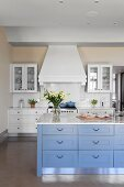 Island counter with blue drawers and marble worksurface in elegant, country-house kitchen with white extractor hood above counter in background