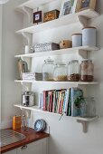 White bracket shelves of storage jars and cookery books in corner of kitchen
