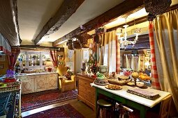 Cluttered country-house kitchen with low, wood-beamed ceiling