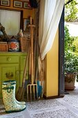 Gardening equipment leaned against green-painted cabinet in storage room