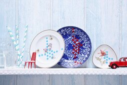 Hand-decorated porcelain plates on wall-mounted shelf