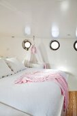 Double bed and cot below portholes in wall