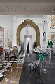 Glass vases on black table and Ghost chairs ni dining room with tall arched doorway with stone surround in background