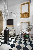 Elegant foyer with chequered floor and modern pendant lamp