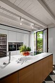 Modern island counter with wooden fronts in rustic room with whitewashed wooden ceiling