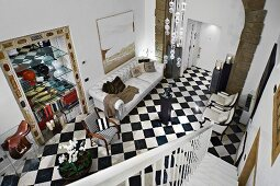 View from staircase into elegant foyer with chequered floor and open-fronted shelves in niche