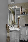 Antique candlestick on washstand below mirror on wall covered in sandy marble tiles