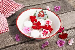 Geranium flowers and candles floating in vintage enamel bowl on wooden table