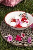 Emailleschüssel mit Schwimmkerzen und Geranienblüten auf Rattanuntersetzer