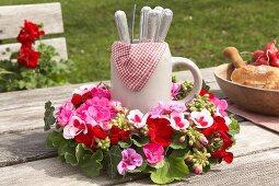 Steinkrug mit Besteck in Kranz aus Geranienblüten, auf Holztisch im Freien