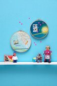 Souvenirs: maps and postage stamps in embroidery hoops decorating wall