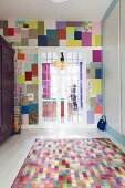 Colourful rug next to fitted cupboard in front of glass sliding doors