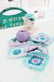 Patchwork-style, pastel crochet blanket being sewn together, crochet needle and ball of purple wool