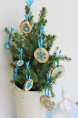 Small fir tree in white, vintage pot decorated with small wooden discs painted with pale blue motifs