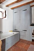 Bathtub with pale grey wooden side and matching fitted cupboard in rustic bathroom with terracotta floor tiles
