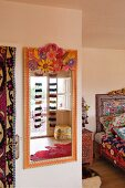 Ethnic-style bedroom with brightly painted mirror and patterned bed