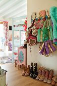 Collection of colourful cowboy boots below various bags hung on coat rack in ethnic-style child's bedroom in pastel shades