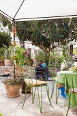 Green metal chairs below pavilion on Mediterranean terrace