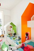 Custom-made house-shaped canopies over children's beds with interiors painted in bright colours; toddler playing on bed