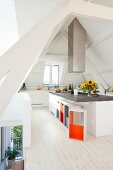 Island counter and designer stools with brightly painted inner surfaces in attic kitchen