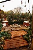 Erhöhter Terrassenbereich mit Feuerstelle gestaltet aus recycelten Holzpaletten