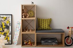 Simple, cubic, modular shelving with bench and nostalgic toys in child's bedroom