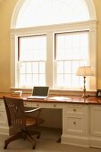 Laptop on traditional desk below large arched window