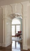 View of dusky pink, wing-back armchair through grand arched doorway