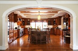 Elegant, spacious, country-house kitchen with wooden fronts, wall units and glossy, exotic-wood parquet flooring