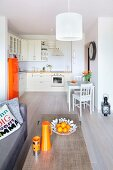 View across coffee table with orange accessories into open-plan kitchen with retro fridge and small dining area